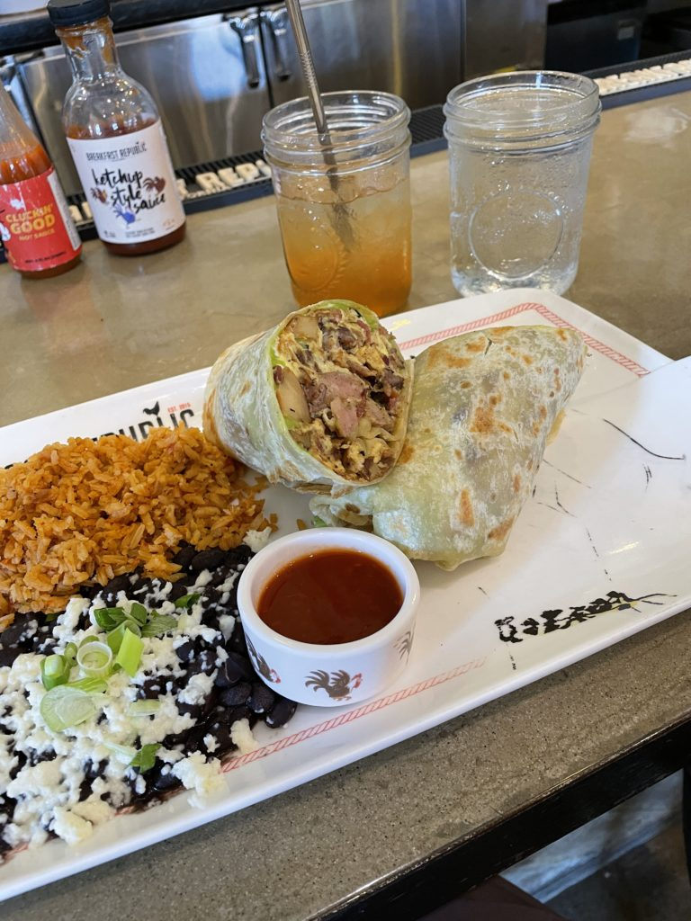 Breakfast burrito and rice on a plate at Breakfast republic at Liberty station in san diego california